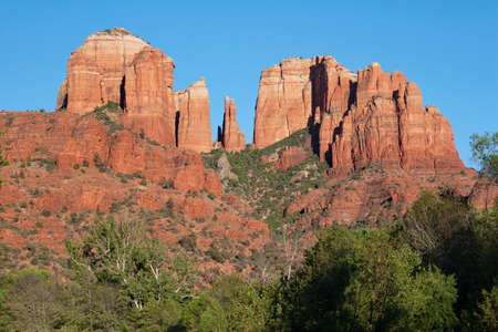 Cathedral Rock above green summer foliage near Sedona, Arizona on cloudless summer day.