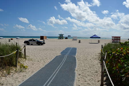 Blocked access to beach and police car in South Beach, Florida during coronavirus pandemic beach and park closures on sunny spring morning.
