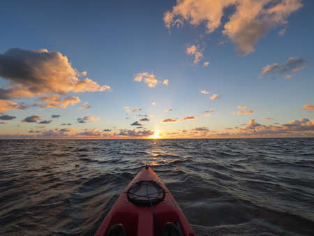 Red kayak pointing toward horizon at sunrise on windy morning in Bear Cur off Key Biscayne, Florida.