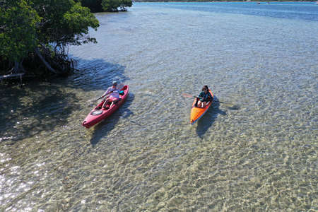 Key Biscayne, Florida - May 5, 2020 - Young couple enjoys afternoon of kayaking on calm, clear water of Bear Cut on sunny May afternoon. 新聞圖片