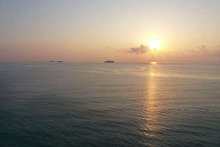Aerial view of sunrise over ocean from Miami Beach, Florida with cruise ships at anchor on horizon.