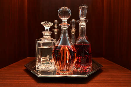 Decanters on silver tray containing variety of liquors on dark wood.