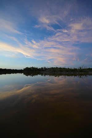 Brilliant colorful clouds in twilight reflected on calm water of Eco Pond in Everglades National Park, Florida on summer evening. 版權商用圖片