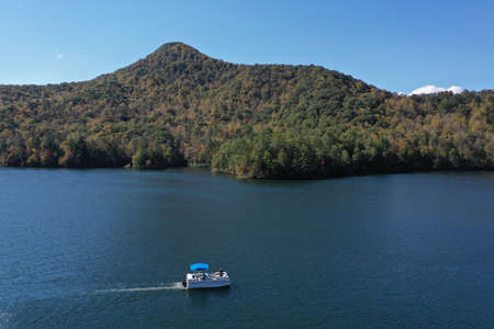 Aerial image of Funnel Top mountain and Lake Santeetlah, North Carolina in autumn color with pontoon boat in foreground.