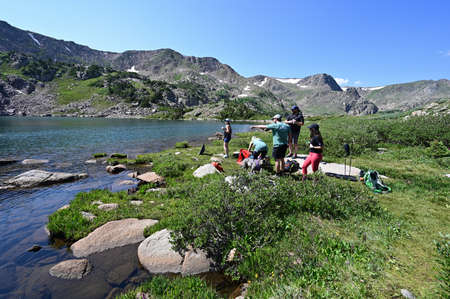 Indian Peaks Wilderness, Colorado - July 27, 2021 - Group of hikers enjoys clear sunny summer afternoon by King Lake in Arapaho National Forest.
