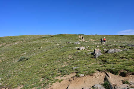 Hikers ascend King Lake Trail in Indian Peaks Wilderness in Arapaho National Forest, Colorado on clear sunny summer afternoon. Stock Photo