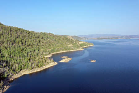 Aerial view of Lake Granby, Colorado and surrounding mountains and forests on clear calm summer morning.