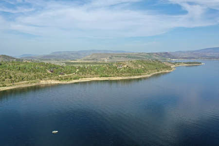 Aerial view of Lake Granby, Colorado and surrounding mountains and forests on calm sunny summer morning. Stock Photo