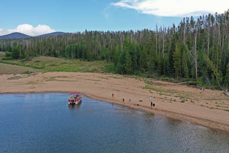 Aerial view of family and friends enjoying afternoon boating on Lake Granby in Arapaho National Recreation Area, Colorado on sunny summer day.