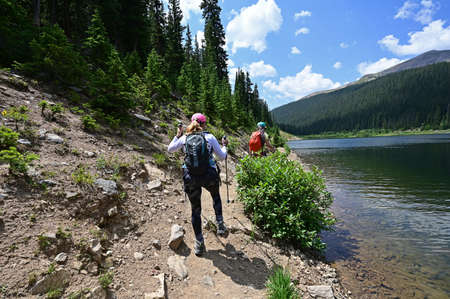 Two young female hikers on shore of Upper Urad Reservoir on Hassell Lake Trail in Arapaho National Forest, Colorado on sunny summer afternoon. Stock Photo