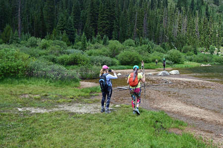 Hikers cross shallow water of Upper Urad Reservoir on Hassell Lake Trail in Arapaho National Forest, Colorado on sunny summer afternoon.
