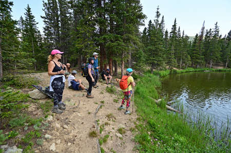 Hikers enjoy view of Hassell Lake in Arapaho National Forest, Colorado on sunny summer afternoon.