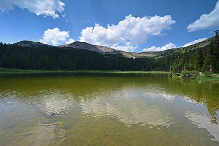 Hassell Lake in Arapaho National Forest, Colorado on sunny summer afternoon with bright cloudscape reflected in water.