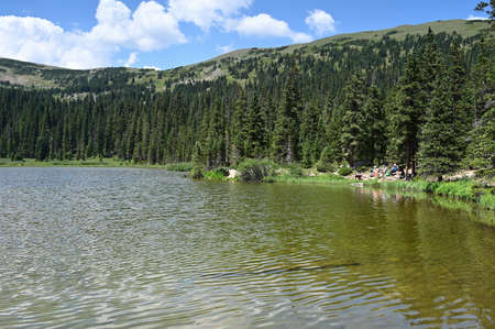 Distant hikers enjoy view of Hassell Lake in Arapaho National Forest, Colorado on sunny summer afternoon.