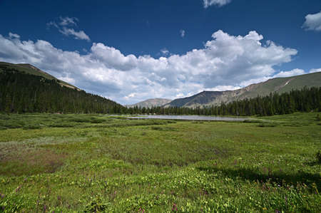 Hassell Lake in Arapaho National Forest, Colorado on sunny summer afternoon under extensive cloudscape.