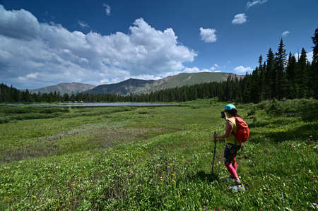 Young female hiker photographs Hassell Lake in Arapaho National Forest, Colorado on sunny summer afternoon.