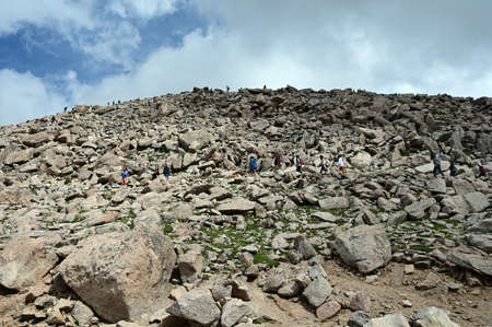 Hikers ascending summit trail on Mount Evans, Colorado under developing summer cloudscape..