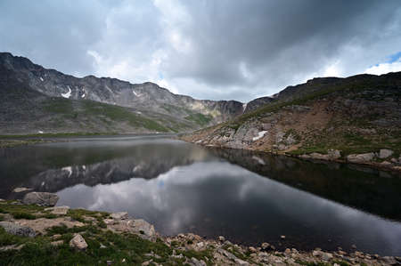 Summit Lake on Mount Evans, Colorado under dramatic summer cloudscape reflected in still water of lake.. Stock Photo