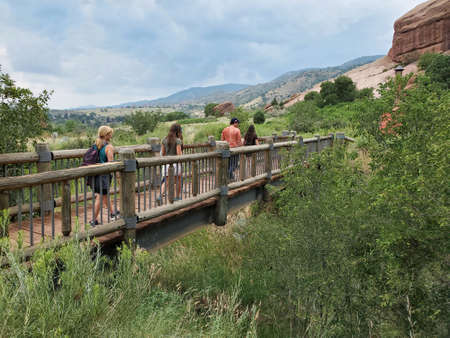 Five young hikers cross bridge on Red Rocks Trading Post Trail near Morrison, Colorado under dramatic summer cloudscape.