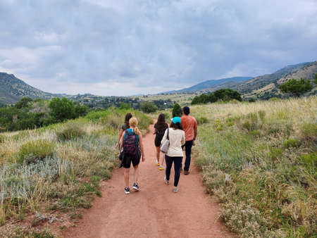 Five young hikers on Red Rocks Trading Post Trail near Morrison, Colorado under dramatic summer cloudscape.