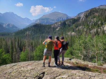 Three young women hikers enjoy view from Emerald Lake Trail in Rocky Mountain National Park, Colorado on sunny summer morning. Stock Photo
