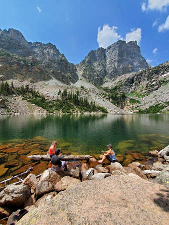 Three young female hikers relax by Emerald Lake in Rocky Mountain National Park, Colorado on sunny summer afternoon.