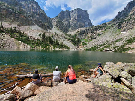 Four young hikers relax by Emerald Lake in Rocky Mountain National Park, Colorado on sunny summer afternoon.