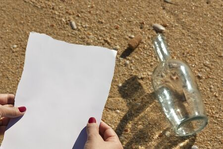 Woman reads the message found in a bottle at the beach (Write your own text) Stock Photo - 10215197