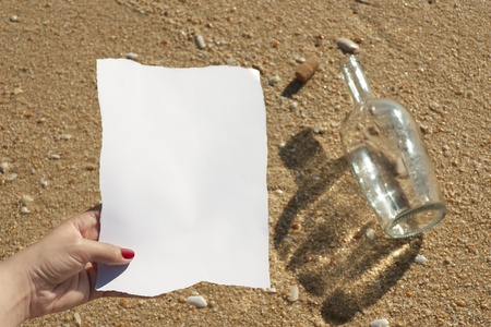 Woman reads the message found in a bottle at the beach (Write your own text) photo