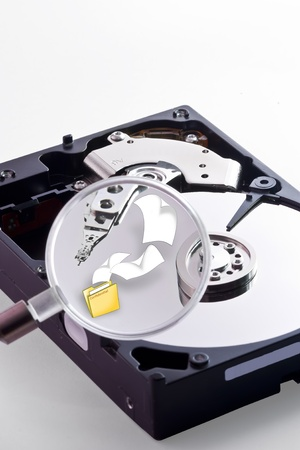 Trying to find some files inside the Hard Disk using a magnifying glass Stock Photo - 10215186