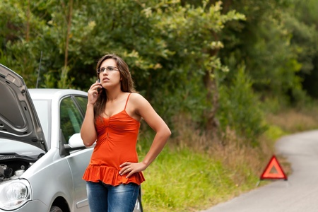 A woman calls for assistance using her mobile phone, after her car broke down on the road side photo
