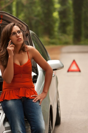 A woman calls for assistance using her mobile phone, after her car broke down on the road side Stock Photo - 10348504