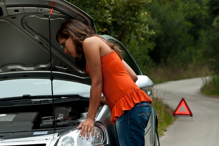 A woman waits for assistance with her car broke down on the road side, after calling for help  Stock Photo