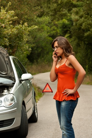 car trouble: A woman calls for assistance using her mobile phone, after her car broke down on the road side