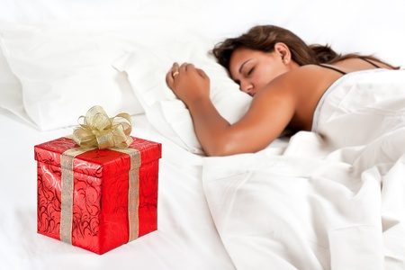 Asleep woman has a surprise present waiting for her in bed Stock Photo