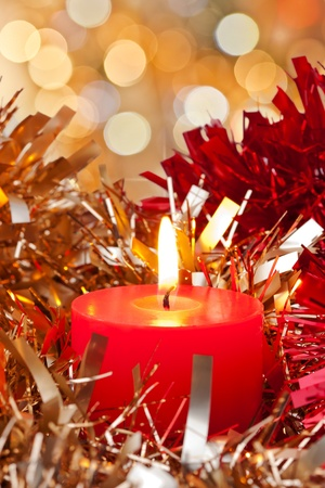 Christmas Candle burning surrounded bit golden and red ribbon Stock Photo