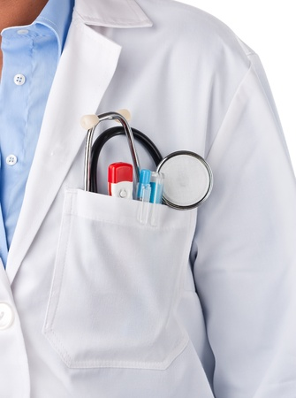 Doctor standing with stethoscope, thermometer and pens inside pocket photo