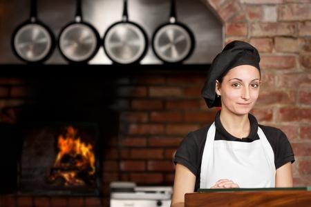 restaurante italiano: Mujer chef est� de pie en la puerta de la cocina con el horno de le�a en el fondo en una cocina de un restaurante de pizza