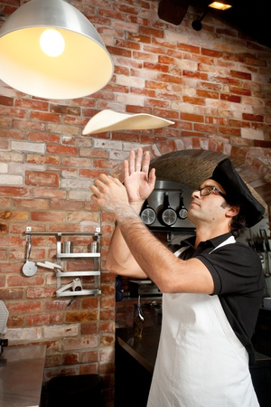 Pizza Chef makes the pizza dough spin in the air to make it thin and soft photo