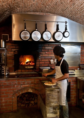 Pizza Chef puts the pizza inside the Wood Oven to bake photo