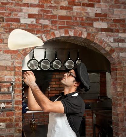 chef italiano: Pizza Chef hace girar la masa de pizza en el aire para que sea fina y suave
