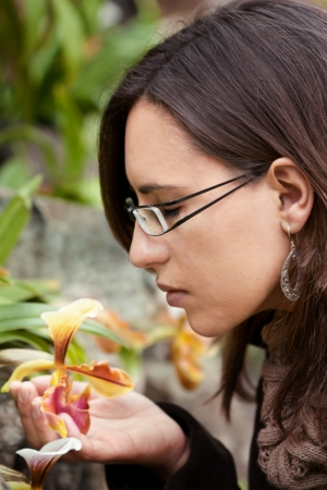 Woman feels the smell of a yellow orchidea flower in Spring