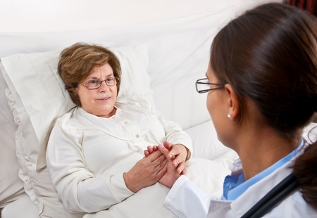 Doctor sitting in bed, comforts recovering senior patient Stock Photo