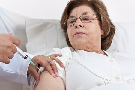 Doctor giving an injection onto a Senior Patient Arm Stock Photo