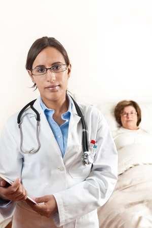 Doctor holding a cardboard with exams with a senior patient in the background Stock Photo