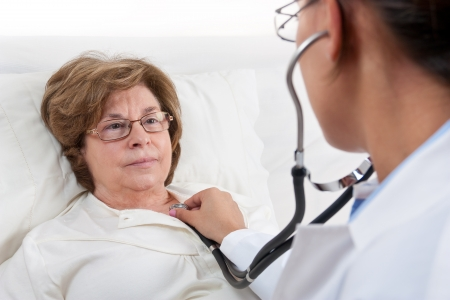 Doctor sitting in bed, examines recovering senior patient photo
