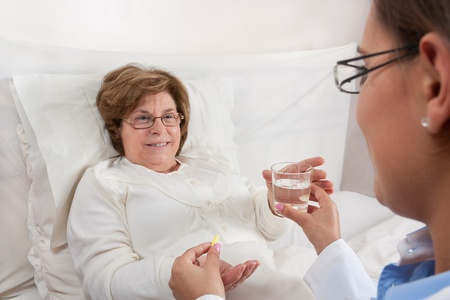Doctor sitting in bed, gives medication and a glass of water to recovering senior patient photo