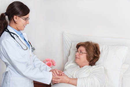 Standing Doctor, comforting recovering senior patient Stock Photo