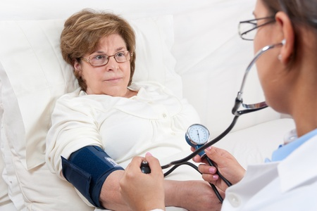 Sitting Doctor is measuring the Blood Pressure on a Senior Patient Stock Photo - 12790858