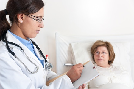 Standing Doctor writes prescription to Senior Patient lying in bed photo